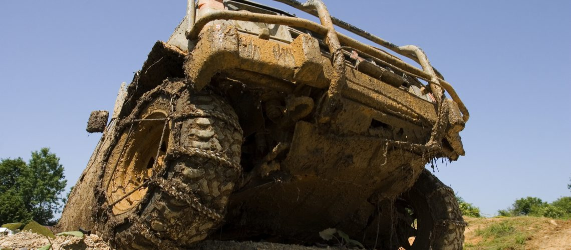 Close-up on a front end of all-terrain vehicle participating in off-road challenge