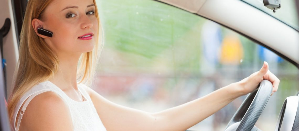 bigstock-Woman-Driving-Car-With-Headset-166118810-1568x1046